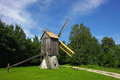 Rural windmill. Scenic old wooden windmill in a countryside, surrounded by a green forest Royalty Free Stock Photos