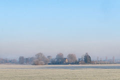 Rural winter landscape with frozen meadow Royalty Free Stock Photo