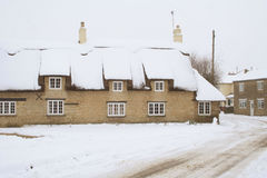Rural winter scene. English village winter scene. Thatched stone cottage in a village lane in the wintertime Stock Photography