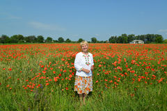 The rural woman costs in a poppy field Stock Photos