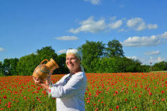 The rural woman drinks water from a jug in a poppy field Royalty Free Stock Images