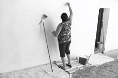 Rural woman painting a traditional spanish white facade in Cadiz Royalty Free Stock Photo
