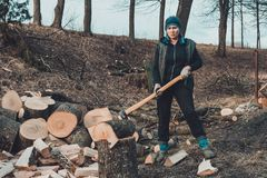 A rural woman shoots an ash tree wood for harvesting for the winter with an ax stock photos