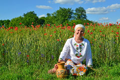 The rural woman sits with a jug in a poppy field Royalty Free Stock Photography