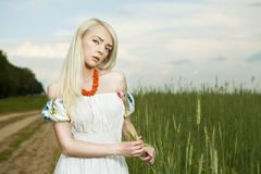 Rural woman standing by the field Royalty Free Stock Image