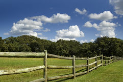 Rural Wooden Fence. With Green Grass and Blue Skies royalty free stock image