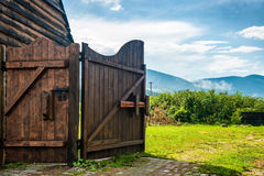 Rural wooden gate and green lawn Royalty Free Stock Photo