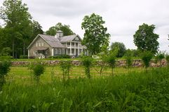 Rural wooden house. Lawn and stones wall Stock Image