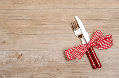 Rural wooden table with red fork and knife. As menu card stock photo