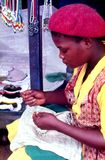 Rural Zulu woman sewing beads at roadside tourist stall. The Zulu women are noted for their colorful bead work of necklaces, headbands, wristbands, and royalty free stock photos