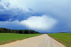 Rurale, campo, strada della ghiaia in Europa, interamente coperta di polvere in mezzo ad un campo verde e di nuvole scure di temp fotografia stock libera da diritti