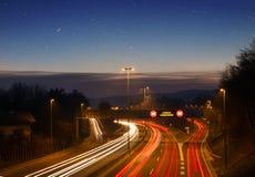 Rusa begreppet av rörande trafik på huvudvägen, motorway på solnedgången arkivbilder
