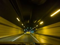 Rusa bilar inom f?r tunnelr?relse f?r huvudv?g en stads- bakgrund f?r suddighet royaltyfri fotografi