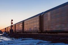 Rusa järnväg bilar på solnedgången med röda signaler Arkivbild