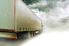 Rusa lastbilen på den snöig vägen arkivfoto