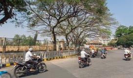 Rusa motorcyklar under träd av de gamla gatorna av den indiska staden Royaltyfri Fotografi