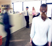 Rush hour 2. Rush hour in the office. Two people discussing in the background, motion blurred persons in the foreground. Conceptual shot for business activities stock images
