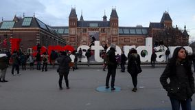 Rush hour in Amsterdam outside Rijksmuseum. Crowd of tourists do a photo near sign `I Amsterdam`. Time Lapse.