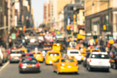 Rush hour with defocused cars and yellow taxi cabs. Traffic jam in Manhattan downtown - Blurred bokeh postcard of New York City with warm sunny day color Stock Photography