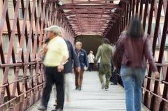 Rush hour in Girona. Blurred people crossing an iron and wood bridge in Girona, Catalonia Royalty Free Stock Image