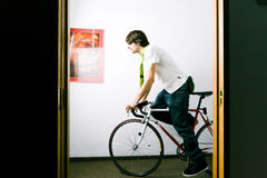 Rush hour at the office. Young employee riding bike to work through office hall at rush hour in the morning royalty free stock photography