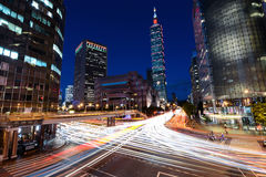 Rush hour traffic speeding through a busy intersection near Taipei 101 in the capital of Taiwan Royalty Free Stock Photo