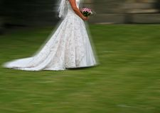Rush me to the Church on time. Motion Blur as Bride dashes towards Chuch entrance with nice detail on dress and text space Stock Photography