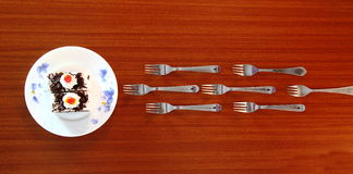 "Rush to dine. Forks and food item ""Cake"" on a wooden background Stock Images"