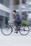 In a rush. Vertical image of an active young businessman on bike in a rush Royalty Free Stock Images