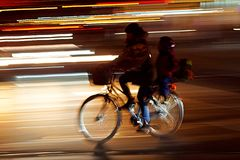 Rushhour with cyclists and child at night stock photography