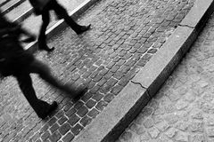 Rushing by. Two pedestrians walking past in the main square in Amsterdam in B&W royalty free stock photography