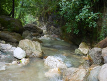 Rushing creek flows through a canyon between rocks of different Stock Photo