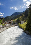 Rushing mountain stream with cabins behind it Royalty Free Stock Photos