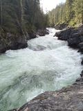 Rushing River. The blue water water coming down from the mountain created by the melting snow provides endless vital resource Royalty Free Stock Photo