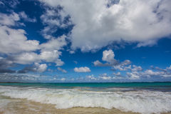 Rushing surf with big sky. Surf rushing in at beach with big sky and clouds shot wide angle Stock Photo