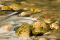 Rushing water. Water flowing around colorful rocks in a river bed Stock Photography