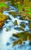 Rushing Water in a Mountain Stream. Water rushes down over rocks and boulders in this mountain stream in the Fargaras Mountains of Romania.  (Negative scan Royalty Free Stock Photo