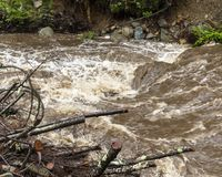 Rushing Water from Severe Flash Flood in Stream. Rushing flash flood water in a stream with fallen trees and branches from heavy rainfall stock photography