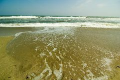 Rushing waves on a sandy beach. Stock Images