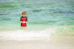 逗人喜爱的7岁红色rushwest游泳衣的男孩在与白色沙子和绿色海洋的热带海滩 免版税库存照片