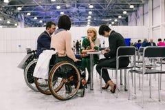 Rusia, ciudad Moscú - 18 de diciembre de 2017: Mujer joven en una silla de ruedas Un grupo de personas que discute un proyecto e foto de archivo