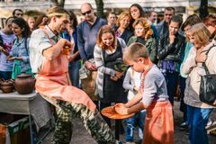 Rusia, ciudad Moscú - 6 de septiembre de 2014: El niño trabaja en una rueda de alfarero Un hombre enseña a un muchacho a hacer un fotografía de archivo libre de regalías
