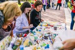 Rusia, ciudad Moscú - 6 de septiembre de 2014: Los niños dibujan en la calle Los adolescentes jovenes se sientan en la tabla y el fotos de archivo