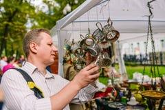 Rusia, ciudad Moscú - 6 de septiembre de 2014: Un hombre elige los prácticos de costa Venta de antigüedades en la calle Reunión d imagen de archivo