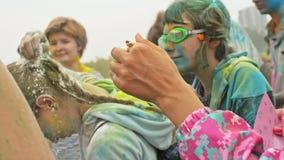 RUSIA, IRKUTSK - 27 DE JUNIO DE 2018: Gente joven feliz que baila y que celebra durante el festival de Holi de colores Muchedumbr