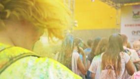 RUSIA, IRKUTSK - 27 DE JUNIO DE 2018: Gente joven feliz que baila y que celebra durante el festival de Holi de colores Muchedumbr metrajes