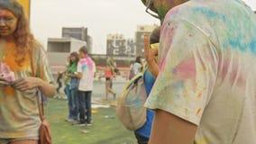 RUSIA, IRKUTSK - 27 DE JUNIO DE 2018: Gente joven feliz que baila y que celebra durante el festival de Holi de colores Muchedumbr almacen de video