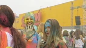 RUSIA, IRKUTSK - 27 DE JUNIO DE 2018: Gente joven feliz que baila y que celebra durante el festival de Holi de colores Muchedumbr almacen de metraje de vídeo