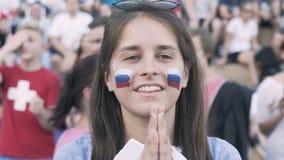 Rusia, Izhevsk - 1 de julio de 2018: Fanático del fútbol femenino ruso que anima en el equipo de fútbol del partido en zona de la almacen de video