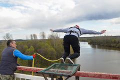 Rusia, Izhevsk, el 14 de mayo de 2017 Salto con una cuerda de la mucha altitud del puente en el río de Izh Foto de archivo